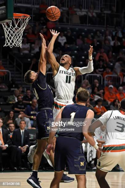 Miami guard Bruce Brown Jr puts up a basket over Navy guard Bryce Dulin in the second half as the University of Miami Hurricanes defeated the Navy...