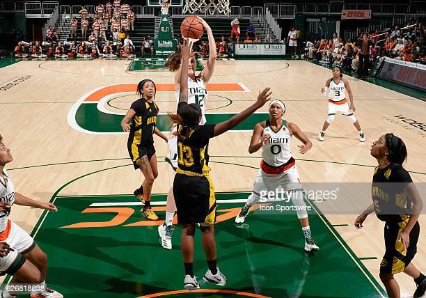 Miami guard/forward Sarah Mortensen shoots against Grambling guard Jazmin Boyd during an NCAA basketball game between Grambling State University...