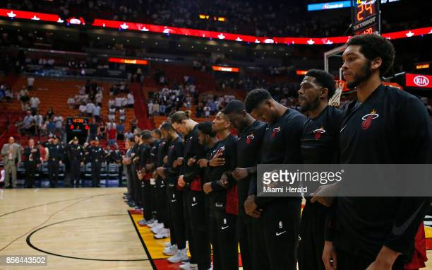 Miami Heat and Atlanta Hawks players lock arms during the playing of the national anthem before an NBA preseason basketball game on Sunday, Oct. 1,...