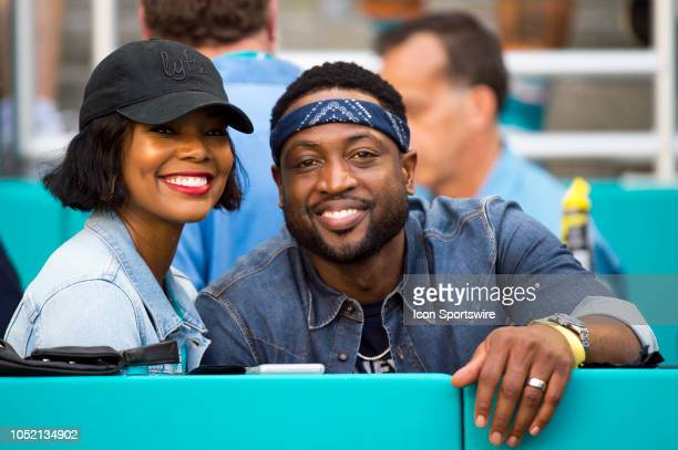 Miami Heat basketball player Dwyane Wade and his wife Gabrielle Union smile as they watch the NFL football game between the Chicago Bears and the...