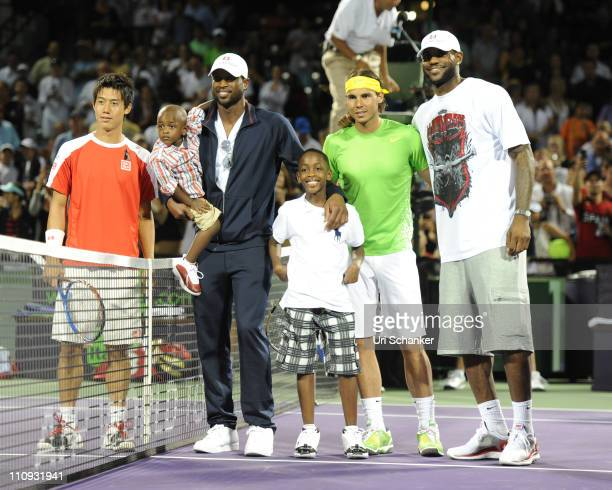 Miami Heat basketball players Dwyane Wade with sons Zion and Zaire and LeBron James pose for photo with tennis players Kei Nishhikori of Japan and...