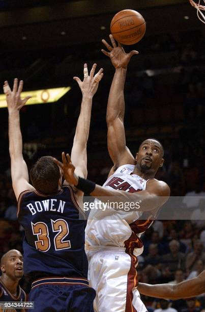 Miami Heat center Alonzo Mourning shoots the ball over Denver Nuggets forward Ryan Bowen in the first half 16 March 2002 at the American Airlines...