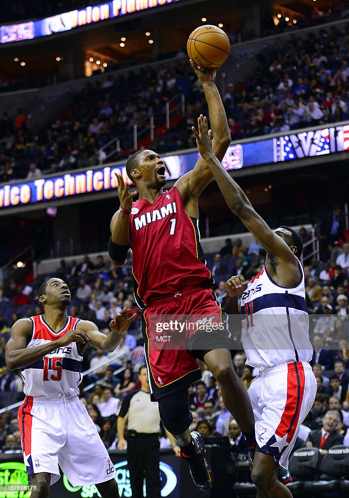 Miami Heat center Chris Bosh (1) puts up a score between Washington Wizards shooting guard Jordan Crawford (15) and Wizards small forward Chris Singleton (31) during first-quarter action at the Verizon Center in Washington, D.C., Tuesday, December 4, 2012.