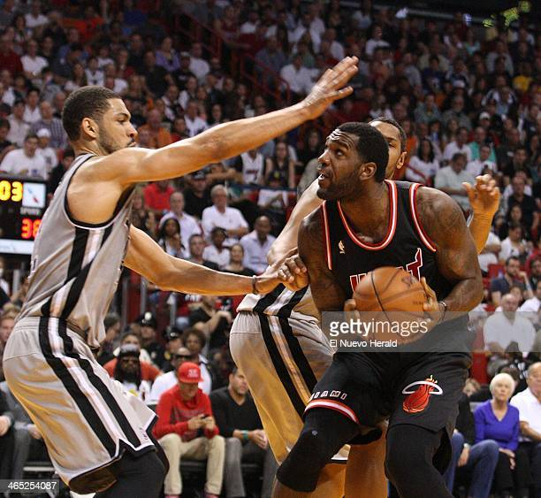 Miami Heat center Greg Oden tries to shoot over San Antonio Spurs center Jeff Ayres in the second quarter at the American Airlines Arena in Miami on...