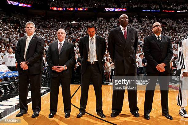 Miami Heat coaching staff members listen to the National Anthem before playing against the Milwaukee Bucks in Game One of the Eastern Conference...