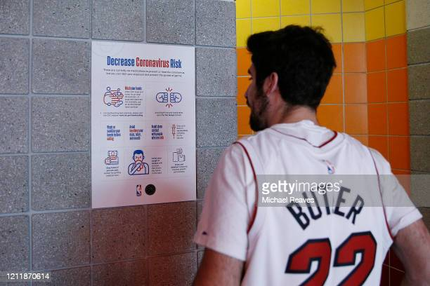 Miami Heat fan looks over a coronavirus poster outside the restroom prior to the game between the Miami Heat and the Charlotte Hornets at American...