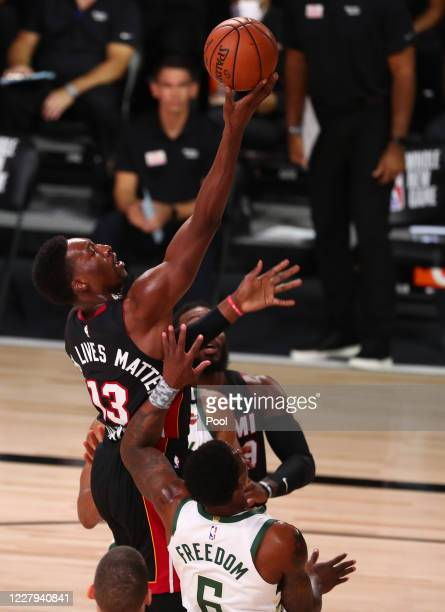 Miami Heat forward Bam Adebayo moves to the basket against Milwaukee Bucks guard Eric Bledsoe during the first half of an NBA basketball game at The...