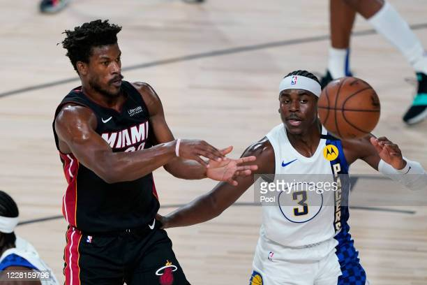 Miami Heat forward Jimmy Butler passes the ball past Indiana Pacers guard Aaron Holiday during the first half of an NBA basketball first round...