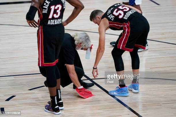 Miami Heat guard Duncan Robinson gives direction as the court is cleaned during a stop in the action during the first half of an NBA basketball first...
