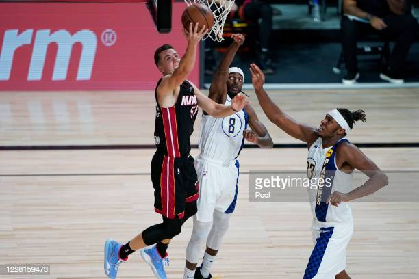 Miami Heat guard Duncan Robinson shoots past Indiana Pacers forward Justin Holiday and center Myles Turner during the second half of an NBA...