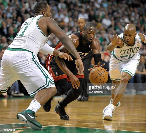 Miami Heat guard Dwyane Wade drives through the defense of the Boston Celtics Glen Davis and Ray Allen during the first half in Game 4 of the NBA...
