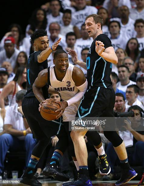 Miami Heat guard Dwyane Wade looks to pass against Charlotte Hornets guard Courtney Lee left and Cody Zelle during the fourth quarter on Wednesday...