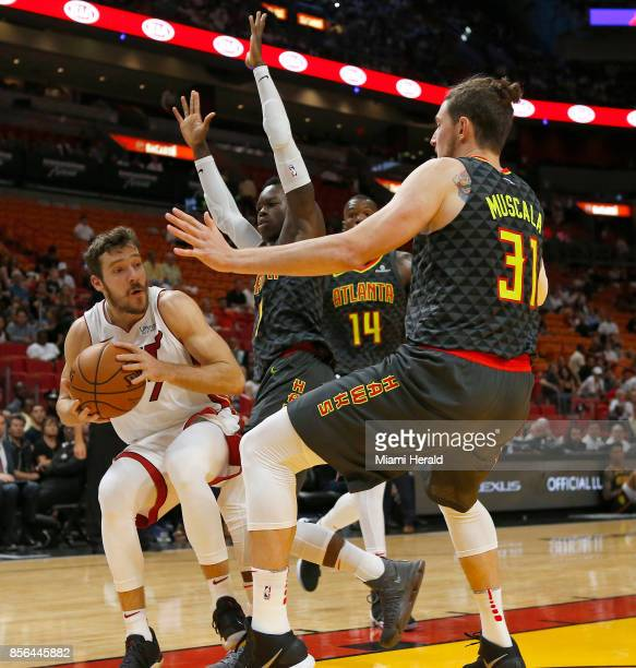 Miami Heat guard Goran Dragic looks to pass against Atlanta Hawks forward Mike Muscala and guard Dennis Schroder during the first quarter of an NBA...