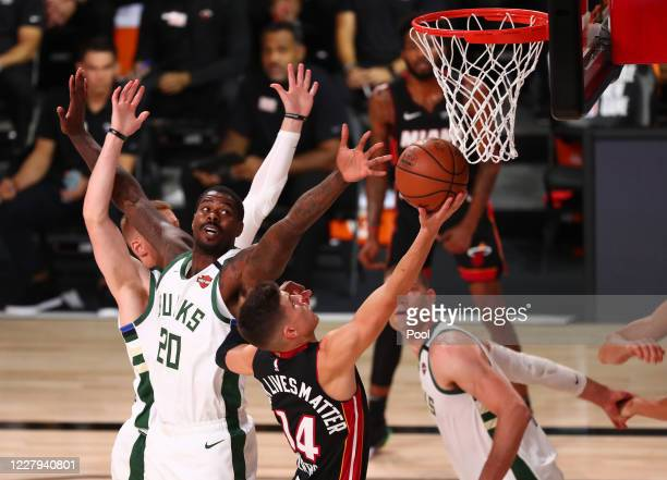 Miami Heat guard Tyler Herro moves to the basket against Milwaukee Bucks forward Marvin Williams during the first half of an NBA basketball game at...