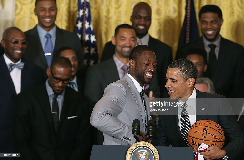 Miami Heat player Dwyane Wade (C) shakes hands with President Barack Obama (R) during an event to honor the NBA champion Miami Heat in the East Room at the White House on January 28, 2013 in Washington, DC. President Barack Obama congratulated the 2012 NBA champions for claiming their third NBA Championship by beating the Boston Celtics.