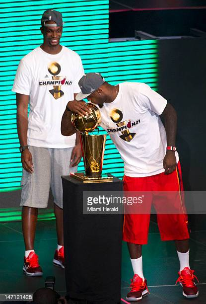 Miami Heat's Chris Bosh left looks on as teammate LeBron James kisses the NBA Championship trophy as the Miami Heat celebrate their NBA world...