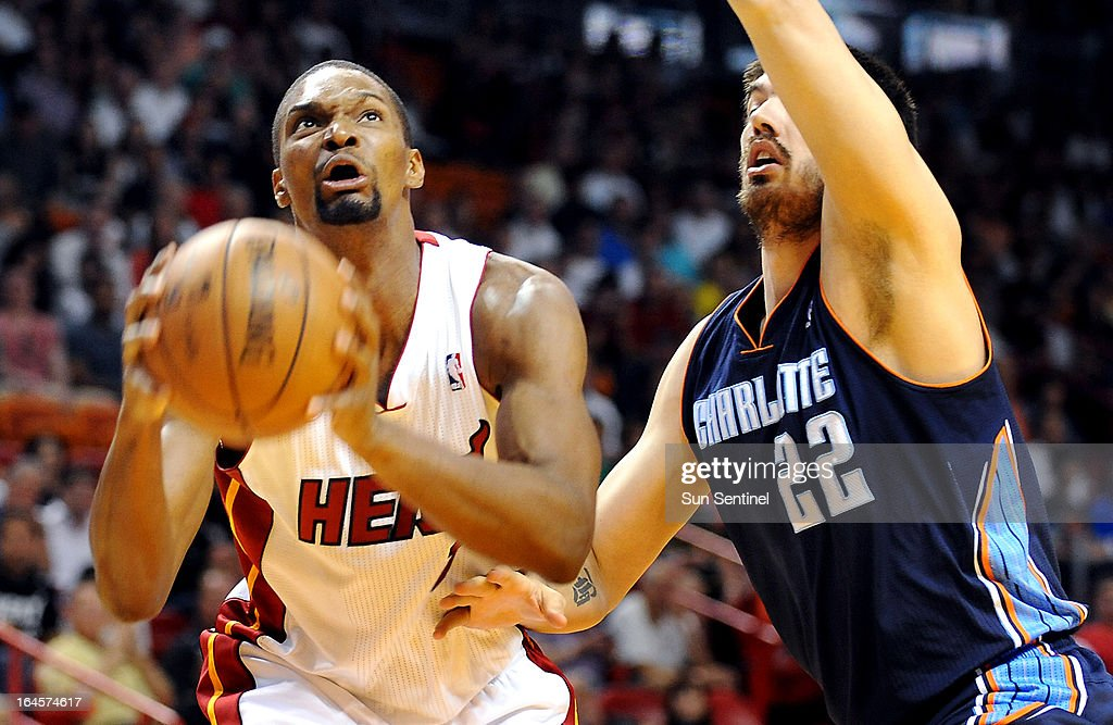 Miami Heat's Chris Bosh looks for position as he is guarded by Charlotte Bobcats' Byron Mullens at AmericanAirlines Arena in Miami, Florida, Sunday, March 24, 2013.