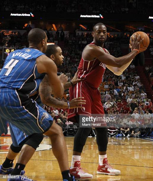 Miami Heat's Dwyane Wade goes to the basket against Orlando Magic's Arron Afflalo and Maurice Harkless during the first quarter at the...