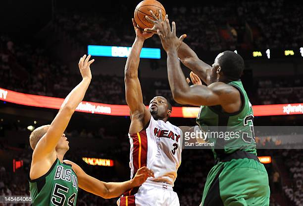 Miami Heat's Dwyane Wade takes a shot between Boston Celtics' Greg Stiemsma left and Brandon Bass right during Game 2 of the NBA Eastern Conference...