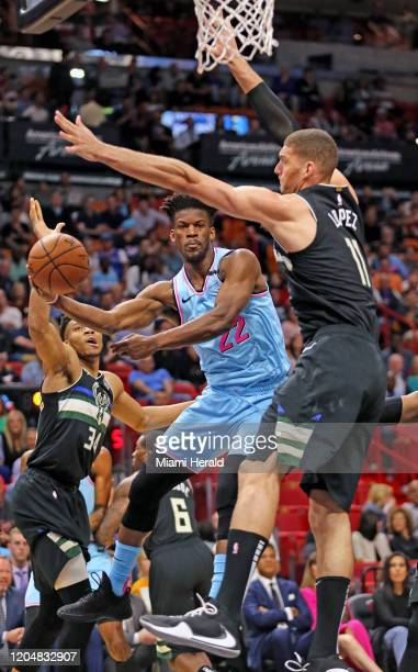 Miami Heat's Jimmy Butler passes the ball under Milwaukee Bucks' Robin Lopez in the first quarter at the AmericanAirlines Arena Monday, March 2, 2020...