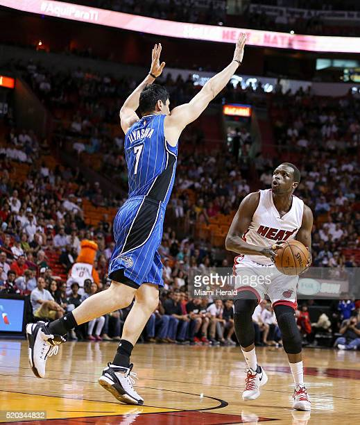 Miami Heat's Luol Deng tries to shoot while Orlando Magic's Ersan Ilyasova blocks during the first quarter on Sunday April 10 at AmericanAirlines...