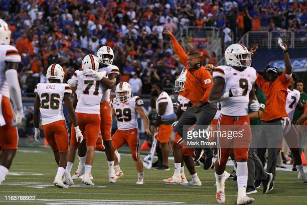 Miami Hurricanes celebrate a fumble recovery by Scott Patchan in the first half against the Florida Gators in the Camping World Kickoff at Camping...