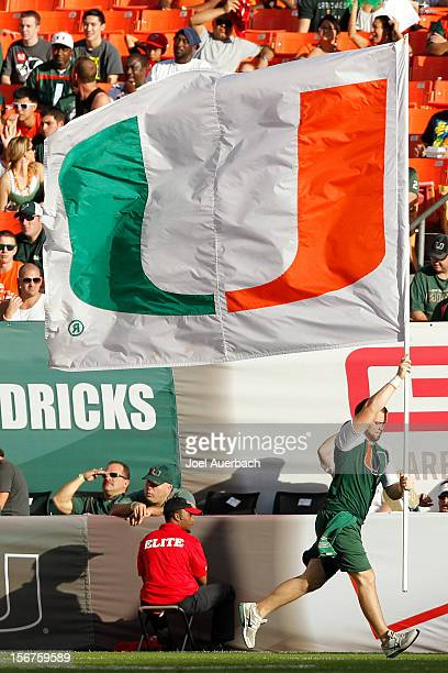 Miami Hurricanes cheerleader runs with a team banner after they scored against the South Florida Bulls on November 17 2012 at Sun Life Stadium in...