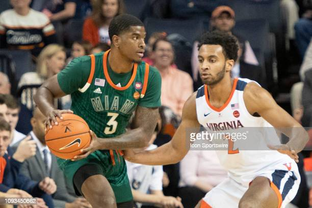 Miami Hurricanes Guard Anthony Lawrence II looks to pass the ball with Virginia Cavaliers Guard Braxton Key defending during the first half of the...