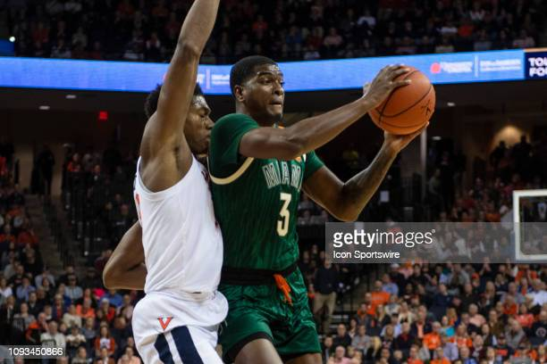 Miami Hurricanes Guard Anthony Lawrence II passes the ball with Virginia Cavaliers Guard De'Andre Hunter defending during the second half of the...
