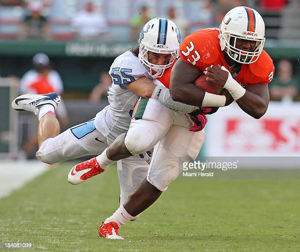 Miami Hurricanes' Maurice Hagens hauls in a first down as North Carolina Tar Heels Tommy Hefferna tackles in the third quarter at Sun Life Stadium in...