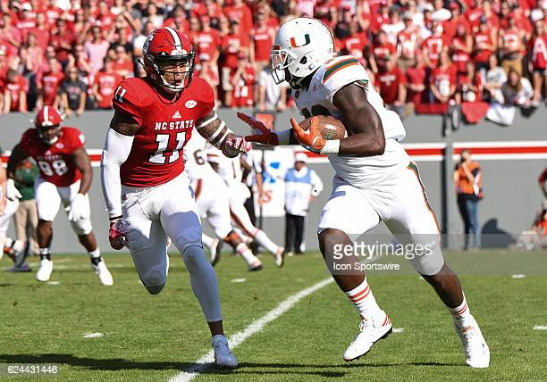 Miami Hurricanes tight end Christopher Herndon IV runs past North Carolina State Wolfpack safety Josh Jones during the first half of the game between...