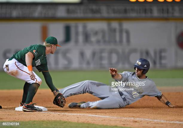 Miami infielder Romy Gonzalez tags out FIU infielder/catcher JC Escarra during a college baseball game between the Florida International University...