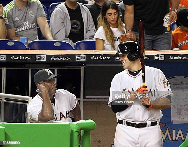 Miami Marlins batting coach Barry Bonds left chats with pitcher Jose Fernandez as he awaits his turn at bat in the second inning against the Arizona...