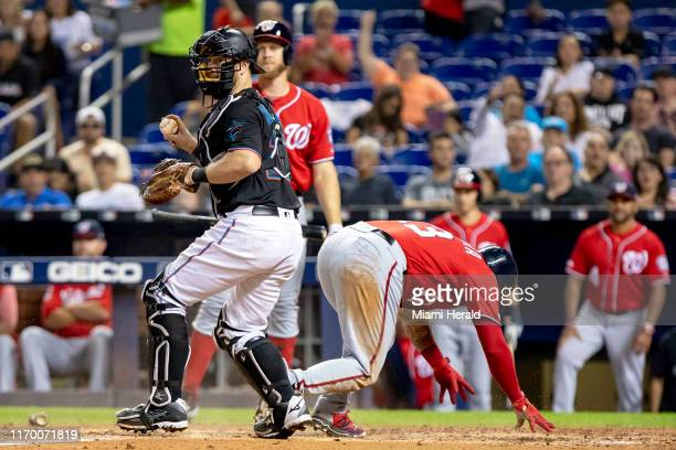 Miami Marlins catcher Bryan Holaday, left, tags out the Washington Nationals' Asdrubal Cabrera at home after a throw from center fielder Magneuris...