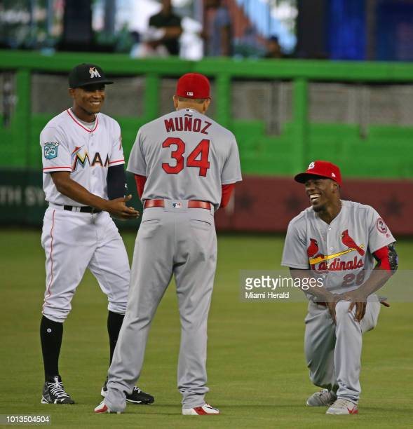 Miami Marlins center fielder Magneuris Sierra talks with St Louis Cardinals third baseman Yairo Munoz and center fielder Adolis Garcia before the...