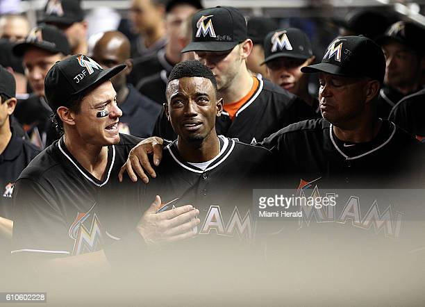 Miami Marlins' Dee Gordon center gets consoled by Derek Dietrich left after hitting a home run during the first inning against the New York Mets on...