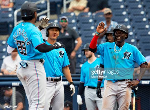 Miami Marlins infiedler Jazz Chisholm and infielder Gosuke Katoh highfive outfielder Jerar Encarnacion at home plate after he homered and led them in...