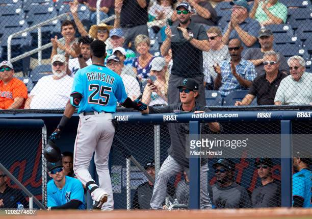 Miami Marlins outfielder Lewis Brinson highfives manager Don Mattingly during the second inning of a spring training game against the Houston Astros...