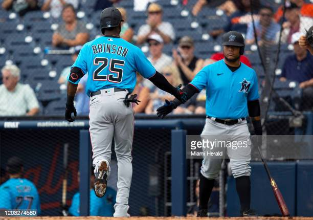 Miami Marlins outfielder Lewis Brinson low fives outfielder Harold Ramirez after homering during the second inning of a spring training game against...