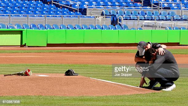 Miami Marlins player Christian Yelich and teammate Justin Bour react in front of a memorial on the pitcher's mound at Marlins Park for Marlins...