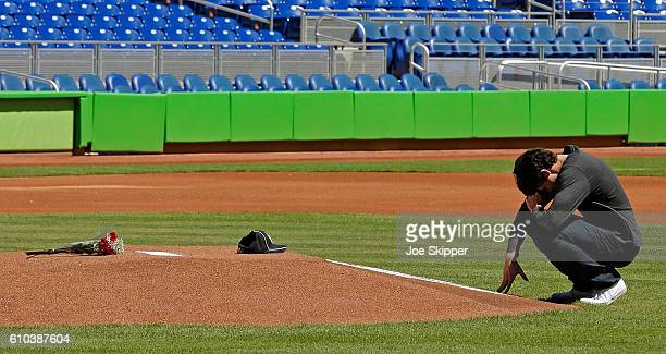 Miami Marlins player Christian Yelich is shown in front of a memorial on the pitcher's mound at Marlins Park for Marlins pitcher Jose Fernanedez who...