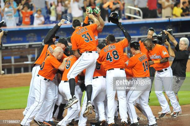 Miami Marlins players celebrate at home plate after Jeff Mathis of the Miami Marlins hitting a grand slam during the ninth inning against the San...