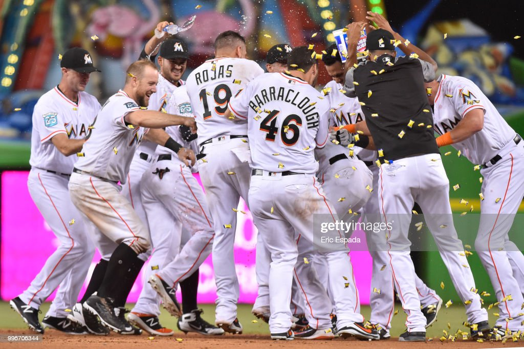 Miami Marlins players congratulate Starlin Castro #13 after he hit a walk off single in the twelfth inning against the Milwaukee Brewers at Marlins Park on July 11, 2018 in Miami, Florida.