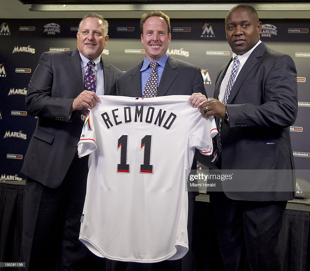Miami Marlins President Larry Beinfest, manager Mike Redmond and Mike Hill, vice president and general manager, hold up Redmon's new uniform as he is introduced at Marlins Park in Miami, Florida, on Friday, November 2, 2012.