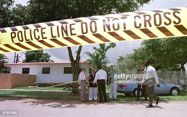 Miami Metro police officers stand 17 July in front of the house of a man who was shot dead inside his home in Miami Springs FL Authorities are...