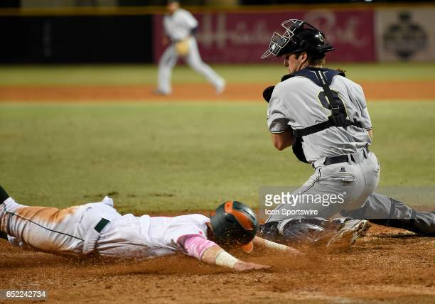 Miami outfielder Carl Chester scores as Georgia Tech catcher Joey Bart is late with the tag during a college baseball game between the Georgia Tech...
