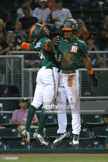 Miami players Tony Jenkins and Freddy Zamora celebrate after scoring on a tworun double by teammate Adrian Del Castillo during the third inning...