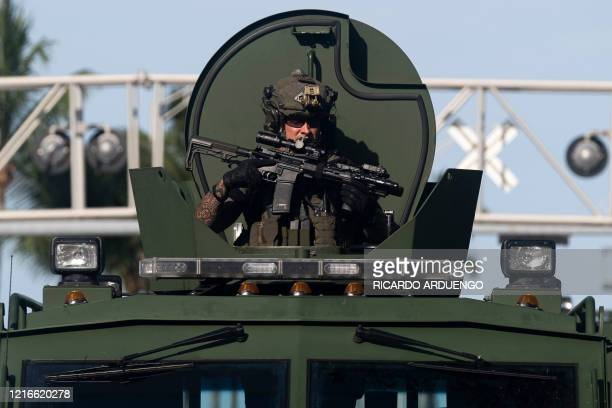 Miami Police officer watches protestors from a armored vehicle during a rally in response to the recent death of George Floyd in Miami, Florida on...