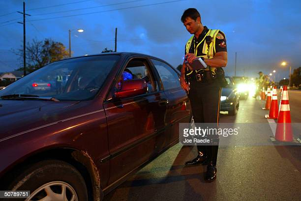 Miami Police Officer William Abraria asks a driver for her identification April 30 2004 in Miami Florida The Miami Police department's traffic...