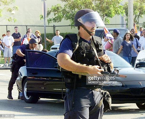 Miami police officers wearing riot gear clear the streets of protestors near the home where Cuban shipwreck survivor Elian Gonzalez had been staying...
